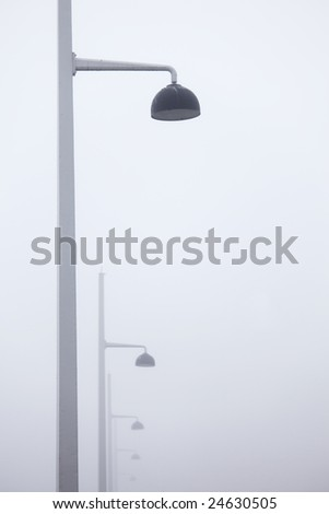 Lined lamps in a misty morning - stock photo