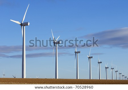 lined mills for production of electric power with cloudy sky - stock photo