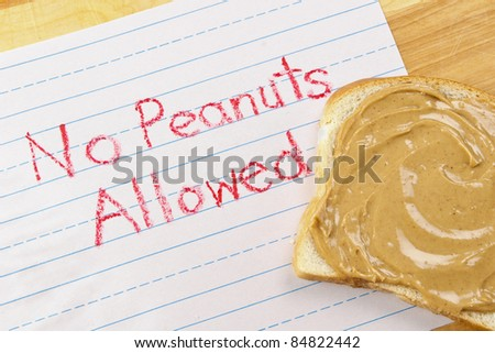 "Lined primary school paper with ""No Peanuts Allowed"" written in red crayon warns against peanut products which are dangerous food allergens"