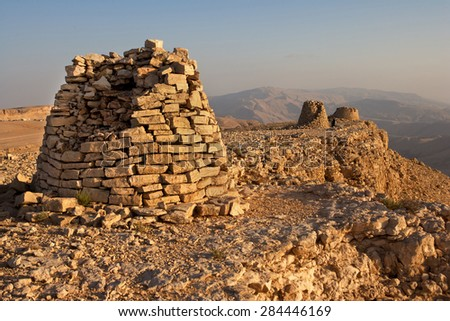 Lined up dramatically atop a rocky ridge, the Beehive Tombs of Bat, in Oman, are 4000-5000 years old and a Unesco World Heritage Site. - stock photo