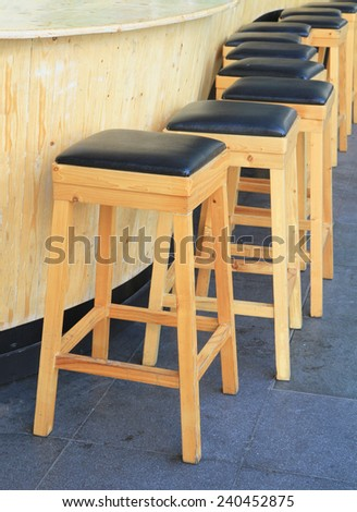 Lined up of wooden bar stools - stock photo