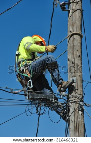 Lineman at work, climbing an electrical pole - stock photo