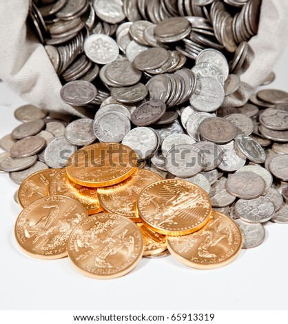 Linen bag of old pure silver coins used to invest in silver as a commodity with a selection of Golden Eagle gold coins - stock photo