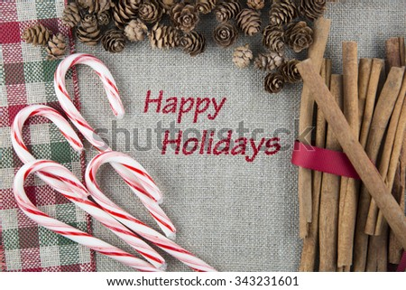 Linen fabric printed with Happy Holidays surrounded by cinnamon sticks, candy canes and pine cones. - stock photo