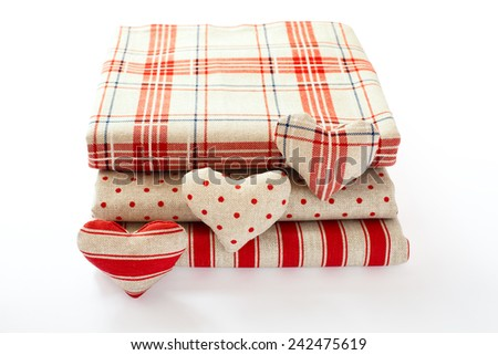linen fabric with red polka dots, plaid and stripes for needlework stacked in a pile isolated. Heart made of cloth.  - stock photo