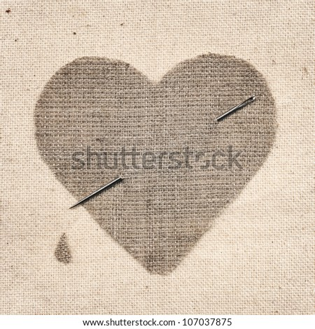 linen heart was pierced by a sewing needle - stock photo
