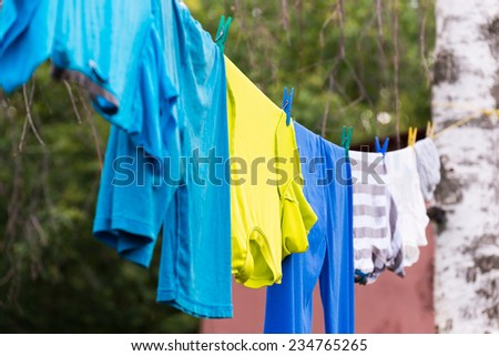 Linen is dried on a rope in the garden - stock photo