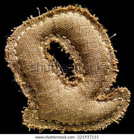 Linen or hemp vintage cloth letter Q isolated on black background
