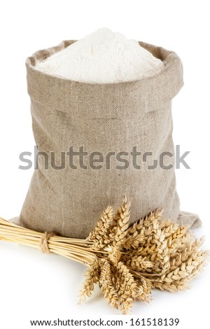 Linen sack full of flour and wheat spike isolated on white background - stock photo