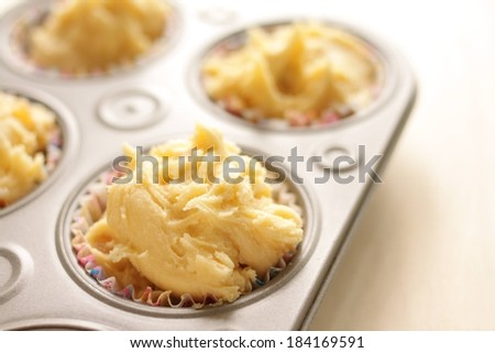 Liners filled with food sitting in a muffin pan. - stock photo