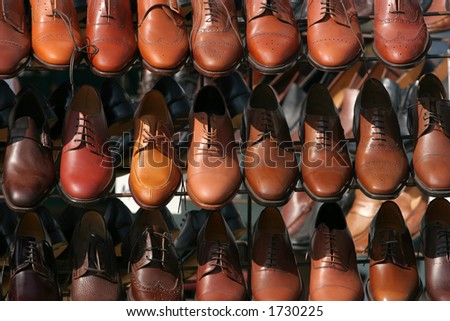 Lines of brown colored mens shoes on a stand. - stock photo