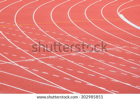 Lines of lanes on red running track - stock photo