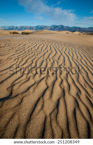 Lines of sand ripples cover the dunes in California's Death Valley National Park. - stock photo