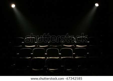 lines of theater chairs in darkness with two reflectors - stock photo