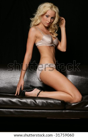 Lingerie Model Kneeling on Couch - stock photo