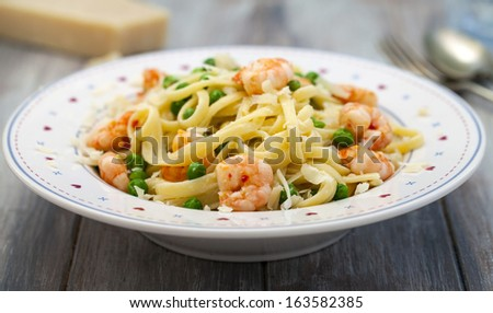 Linguine pasta with prawns and green peas  - stock photo