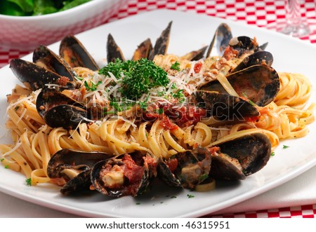 Linguini with baby clams and fresh mussels in tomato sauce with parmesan cheese and fresh herbs, accompanied buy lettuce salad and red wine - stock photo