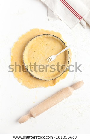 Lining a fluted tart tin with shortcrust pastry dough, base pricked with a fork. Taken on a floured white surface, directly from above with rolling pin and kitchen towel. - stock photo