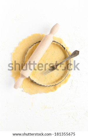 Lining a fluted tart tin with shortcrust pastry dough, base pricked with a fork. Taken on a floured white surface, directly from above with rolling pin, and vintage fork. - stock photo