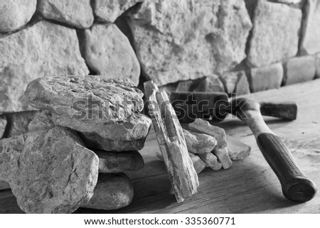 Lining the walls of the wild flat stone, limestone and construction hammer. Black and white images - stock photo