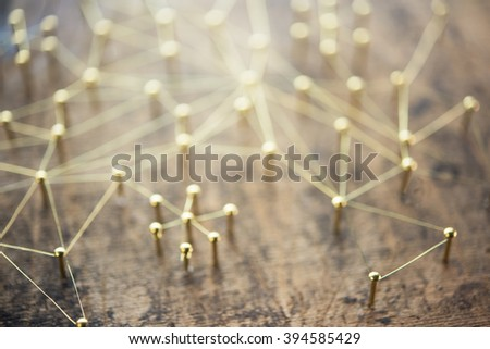 Linking entities, blurred background, or off-focus background. Network, networking, social media, internet communication abstract. Web of gold wires on rustic wood. - stock photo