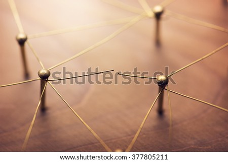 Linking entities. Broken connection or broken relation. Network, networking, social media, internet communication abstract. Web of gold wires on rustic wood. - stock photo