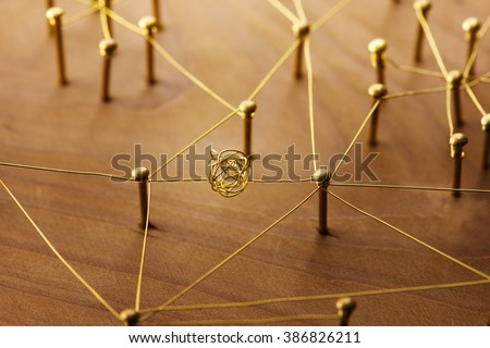 Linking entities. Dispute or conflict, or Bottleneck  between two entities. Network, networking, social media, internet communication abstract. Web of gold wires on rustic wood. - stock photo