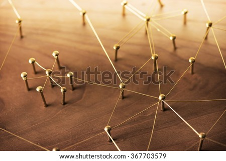 Linking entities. Network, networking, social media, internet communication abstract. A small network connected to a larger network. Web of gold wires on rustic wood. - stock photo