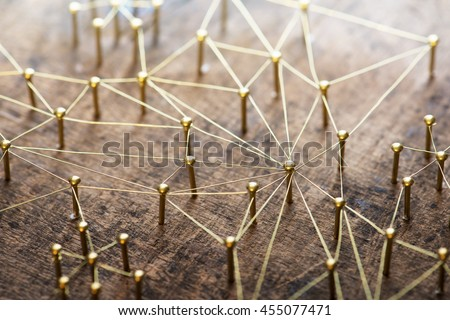 Linking entities. Network, networking, social media, internet communication abstract. Many small network connected to a larger network. Web of gold wires on rustic wood. . Shallow Depth of field. - stock photo