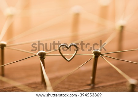Linking entities. Network, networking, social media, internet communication abstract. Online love or matching. Web of gold wires, with one connection having a heart. - stock photo