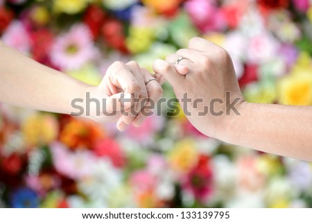 Linking little fingers with somebody to confirm promise - stock photo