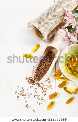 Linseed and flaxseed oil capsules over white wooden background - stock photo