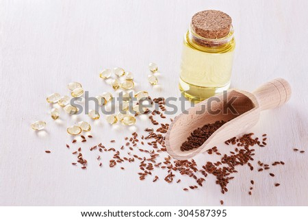 Linseed, flaxseed oil capsules and flaxseed oil over white wooden background - stock photo