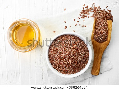 Linseed oil and bowl of linseeds on white wooden background. Top view