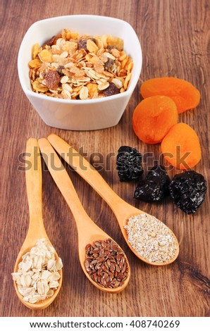 Linseed, rye flakes and oat bran on spoon, dried fruits and muesli, concept of healthy nutrition and increase metabolism, ingredients with dietary fiber - stock photo