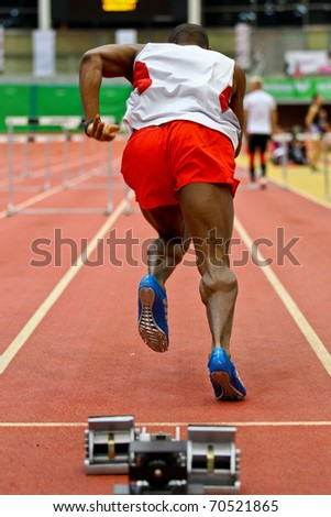 LINZ,  AUSTRIA - FEBRUARY 3 Linz indoor track and field meeting.  Selim Nurudeen (Nigeria)takes part in the men's 60m hurdles event on February 3, 2011 in Linz, Austria. - stock photo