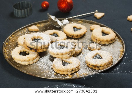 linzer cookies with red christmas ornaments on black canvas background