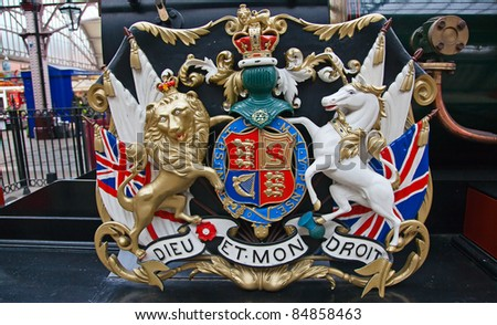 Lion and unicorn on English heraldic coat of arms on an ancient steam train in Windsor - stock photo