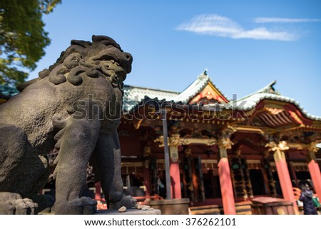 Lion-dog nad the Main Hall of Nezu shrine in Tokyo, Japan