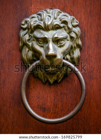 Lion door knocker on wooden door - stock photo