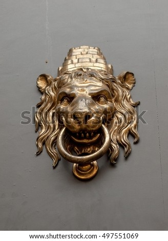 Lion head door handle in Barcelona, golden on grey