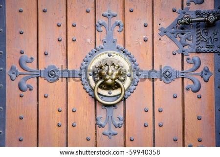 Lion head doorknocker on old-fashioned wooden door with metal elements - stock photo