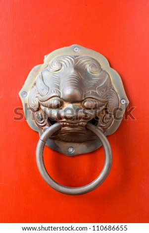 lion knocker on the chinese traditional red door of temple in Ba (but, if there is artist name, it only for tell who is the artist of work, not for copyright)