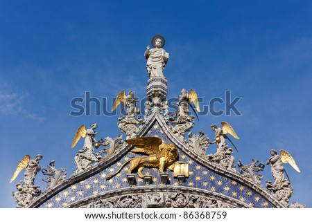 Lion of St Mark and angels on a detail of the facade of St Mark's Cathedral in Venice, Italy - stock photo