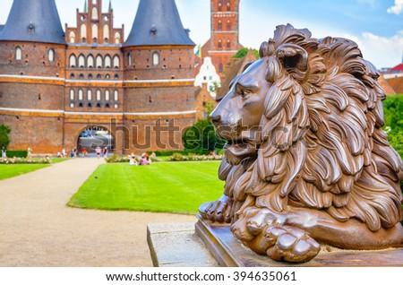 Lion statue beside Holstein Gate at Lubeck. Schleswig-Holstein, Germany - stock photo
