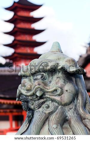 Lion statue guarding the entrance to the Miyajima Shrine, Miyajima Island, near Hiroshima, Japan. The shrine and the five story pagoda are in close proximity. - stock photo