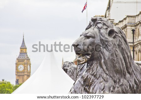 Lion statue in the Monument and the Big Ben, London - stock photo