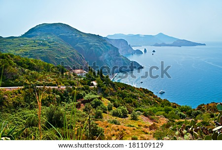 Lipari Island boasts its lush vegetation because of reach volcanic soils and indented coastline with a view on the smoking crater of Volcano Island, Aeolian Islands, Italy. - stock photo