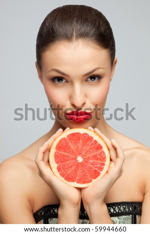 Lips or fruit? A portrait of a tasty woman holding a juicy grapefruit under her chin. - stock photo