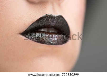 Lips painted with black lipstick with sparkles